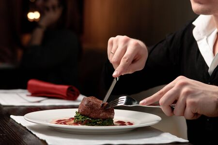 elegantly: A handsome young man eating delicious meat cutlet with a knife and fork at a table elegantly served