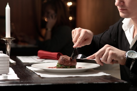 A handsome young man eating delicious meat cutlet with a knife and fork at a table elegantly served Stock Photo - 11123708