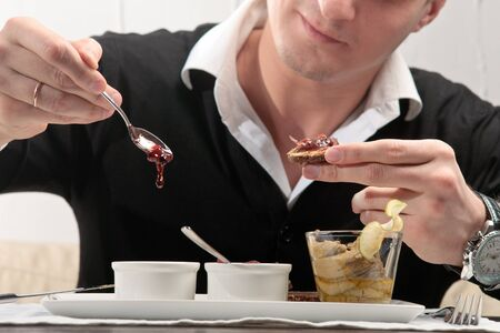 elegantly: A young man spreading cherry jam on a piece of bread, sitting at an elegantly served table in a restaurant Stock Photo