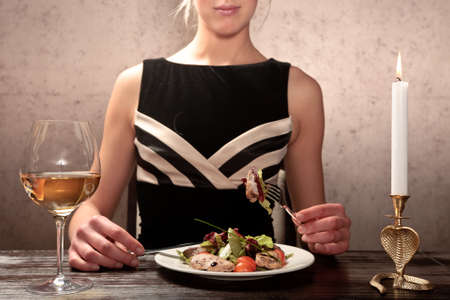 elegantly: A young woman eating meat salad with stewed and fresh vegetables at an elegantly served table in a restaurant