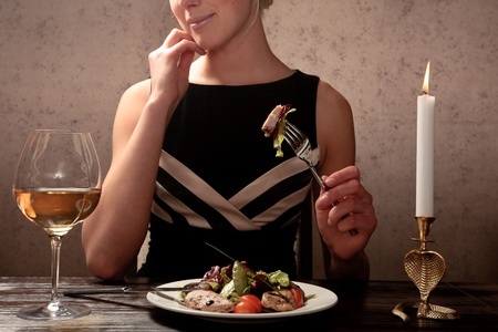 A young woman eating meat salad with stewed and fresh vegetables at an elegantly served table in a restaurant photo