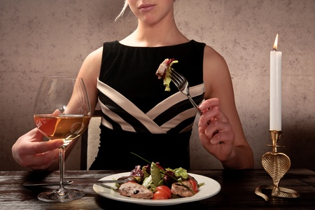 A young woman eating meat salad with stewed and fresh vegetables at an elegantly served table in a restaurant