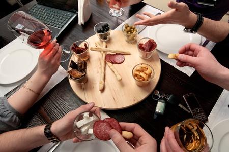 lunchen: Business lunch - Groep mensen eten lunch uit een set van heerlijke pittige snacks