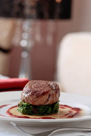 Meat cutlet placed on a spinach cutlet on a white plate decorated with tomato sauce, on a table elegantly served photo