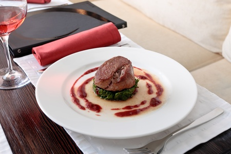 Meat cutlet placed on a spinach cutlet on a white plate decorated with tomato sauce, on a table elegantly served