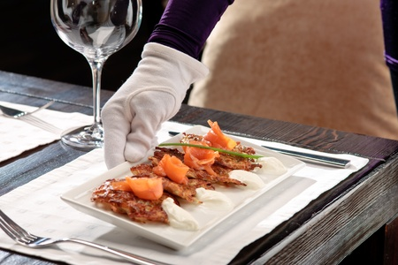 Crispy potato pancakes decorated with salmon and sour cream being served by a waiter photo