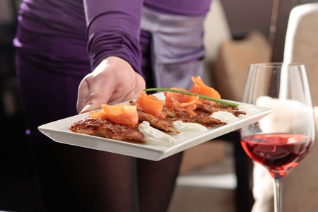 Crispy potato pancakes decorated with salmon and sour cream being served by a waiter Stock Photo