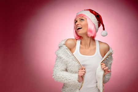 Beautiful happy young woman wearing pink wig and dressed as santa over red background. Stock Photo