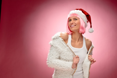 Portrait of a beautiful young woman in pink wig wearing christmas clothes over red background. Stock Photo