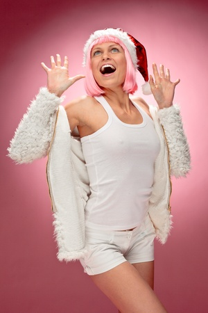Portrait of a beautiful young woman in pink wig wearing xmas clothes over red background.