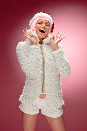 Portrait of a beautiful young woman in pink wig wearing xmas clothes over red background. photo