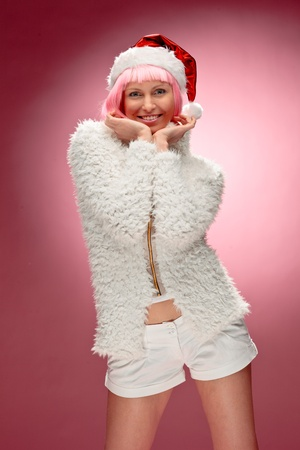 mrs claus: Portrait of a beautiful young woman in pink wig wearing xmas clothes over red background.