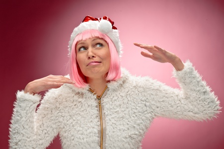 Portrait of a beautiful young woman in pink wig wearing christmas clothes over red background. photo