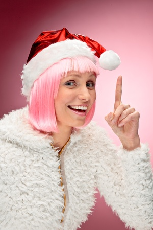 Studio portrait of beautiful happy young woman wearing pink wig and dressed as santa over red background.