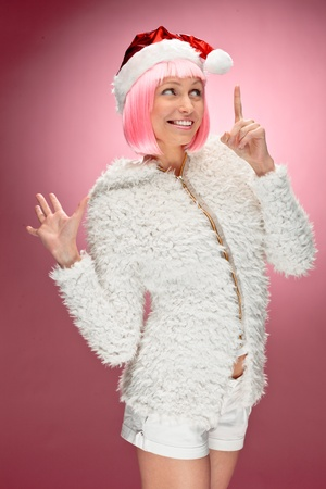 Studio portrait of beautiful happy young woman wearing pink wig and dressed as santa over red background. photo
