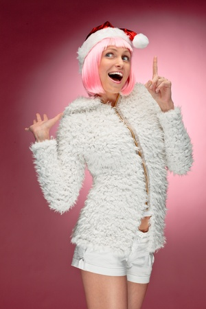 Studio portrait of a sexy young woman in pink wig dressed as Santa Stock Photo