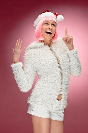 Studio portrait of a sexy young woman in pink wig dressed as Santa photo