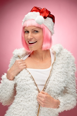 Studio portrait of a sexy young woman in pink wig dressed as Santa over red background.  Stock Photo
