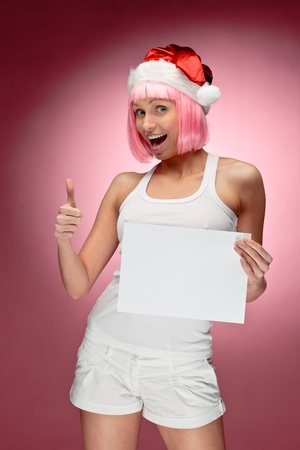 Female santa holding a christmas clear white card over red background photo