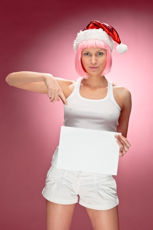 Attractive Female santa holding a christmas clear white card over red background photo