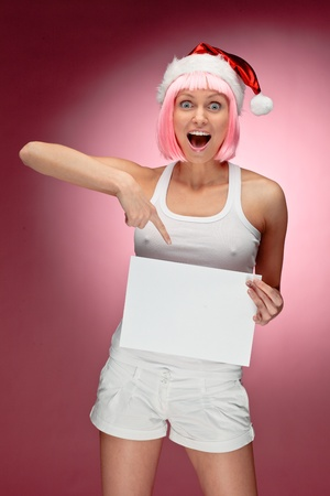 Attractive female santa holding a christmas clear white card over red background Stock Photo - 11229037