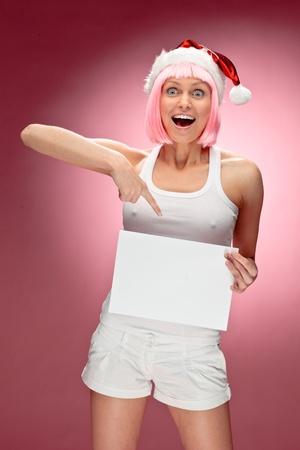 señora: Atractivo de santa mujer sosteniendo una tarjeta de navidad blanca transparente sobre fondo rojo Foto de archivo