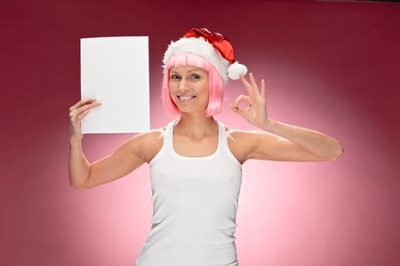 Sexy female santa holding a christmas clear white card over red background photo