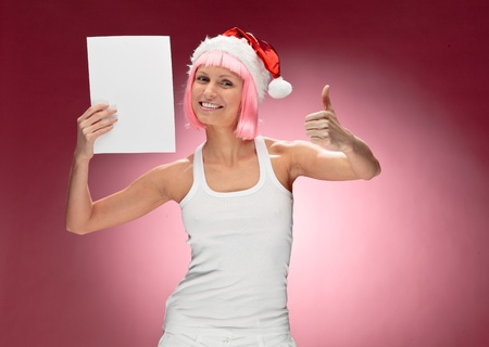 Beautiful female santa in pink wig holding a christmas clear white card over red background photo