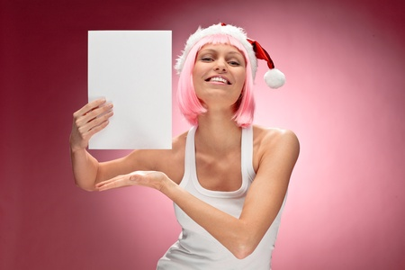dona: Joven mujer en Santa peluca rosa celebración de una tarjeta de navidad blanca transparente sobre fondo rojo Foto de archivo