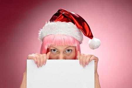 dona: Joven de santa mujer con peluca rosa que sostiene una tarjeta de Navidad blanca transparente sobre fondo rojo Foto de archivo