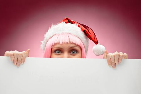 Young female santa in pink wig holding a christmas clear white card over red background photo