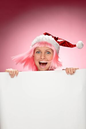 Young female santa in flaunting pink wig holding a christmas clear white card over red background Stock Photo - 11227468