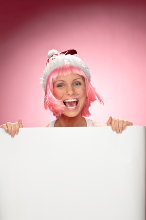 Young female santa in flaunting pink wig holding a christmas clear white card over red background photo