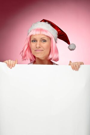 Young female santa in flaunting pink wig holding a christmas clear white card over red background Stock Photo - 11227352