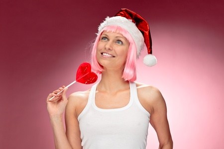 Young female santa in flaunting pink wig with a heart lollypop over red background photo