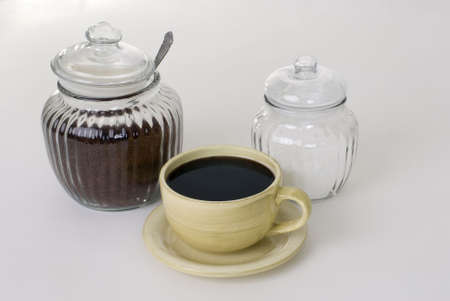 coffee hour: A jar of sugar and coffee and a cup of coffee.