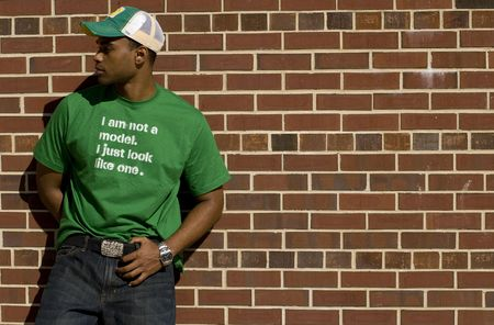Attractive young African American male playing posing in a green t-shirt and jeans against a brick wall. 免版税图像