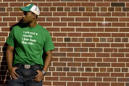Attractive young African American male playing posing in a green t-shirt and jeans against a brick wall. Stock Photo - 3024346
