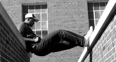 매력적인 젊은 아프리카 계 미국인 남성 T- 셔츠, 청바지, 야구 모자에서 포즈를 재생합니다.