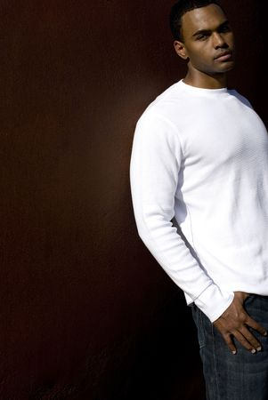 african american male: Attractive young African American male playing posing in a white t-shirt and jeans against a solid brown wall.