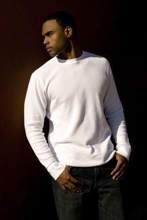 매력적인 젊은 아프리카 계 미국인 남성 흰색 t- 셔츠와 청바지 단단한 갈색 벽에 포즈를 재생합니다. 스톡 콘텐츠