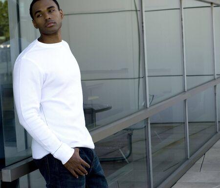 매력적인 젊은 아프리카 계 미국인 남성 화이트 티셔츠와 청바지 유리에 포즈 재생. 스톡 콘텐츠
