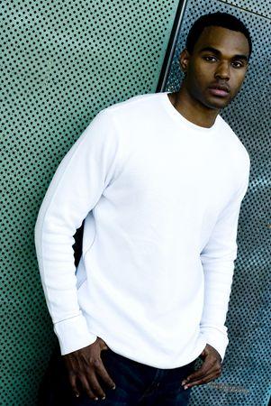 매력적인 젊은 아프리카 계 미국인 남성 재생 백인 티셔츠와 청바지에 포즈. 스톡 콘텐츠