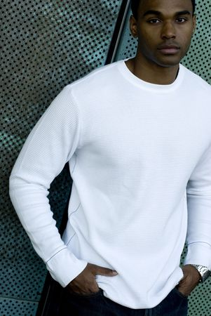 Attractive young African American male playing posing in a white t-shirt and jeans against a mesh green wall.