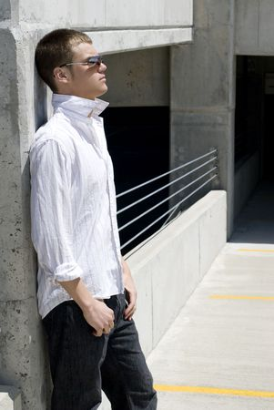 A young man outside against a wall.