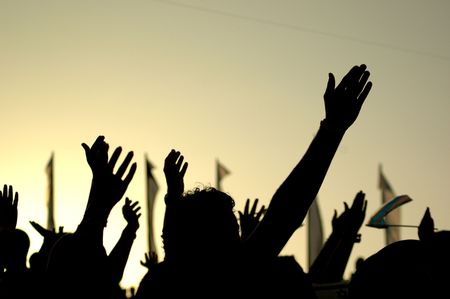raises: A crowd of people in silhouette raises their hands against the background of a yellow sunset. Stock Photo