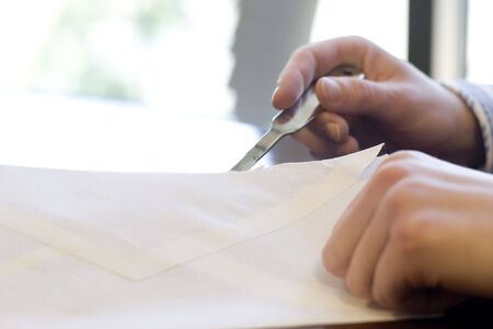 In an office setting, the hands of an office worker are shown using a letter opening knife to slice open an envelope. photo