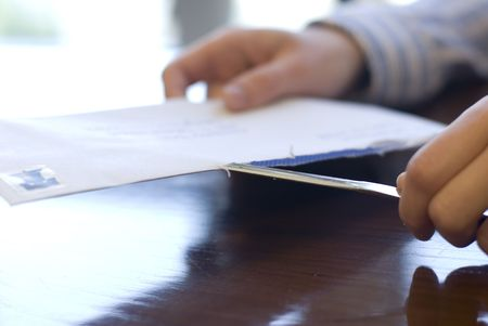In an office setting, the hands of an office worker areshown using a letter opening knife to slice open an envelope.