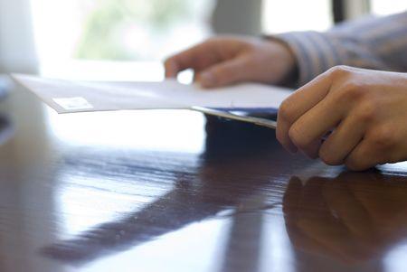 In een kantoor omgeving zijn de handen van een kantoor werknemer weer gegeven met behulp van een brief opening mes slice open een envelop. Stockfoto
