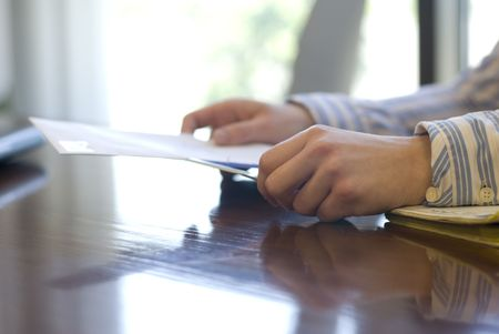 private information: In an office setting, the hands of an office worker are shown using a letter opening knife to slice open an envelope. Stock Photo